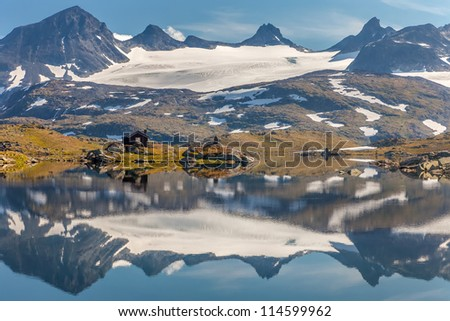Lonely little wood house near glacier and mountain lake - stock photo