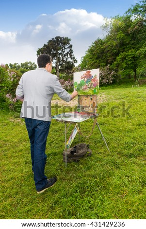 Lonely male artist  working outdoors in the park or garden on a trestle and easel painting with oils and acrylics during an art class - stock photo
