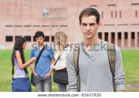 Lonely male student posing while his classmates are talking outside a building - stock photo