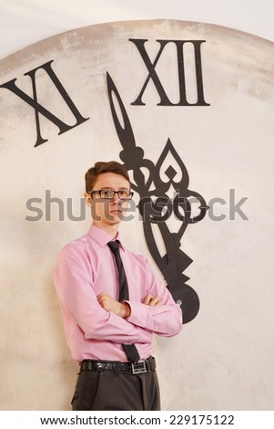 Lonely man one expects the new year. Man standing near the clock. Arrows show the big clock time. The clock at five minutes to twelve. Time of onset of the new year. Five minutes to midnight. - stock photo