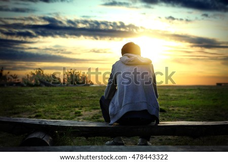 Lonely Man sit on the Bench at Sunset Background