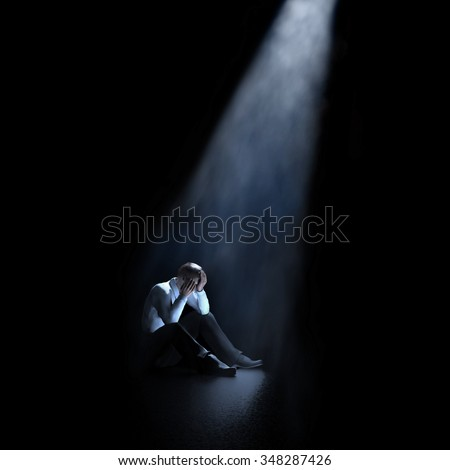 lonely man sitting in a dark room - stock photo