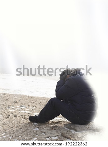 Lonely man sitting on sand in a winter day - stock photo