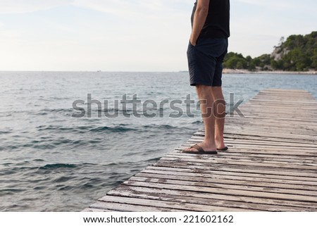 lonely man standing on pier - stock photo