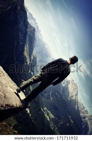 Lonely man standing on the edge of a canyon - stock photo