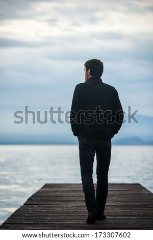 Lonely man walking on a lake dock - stock photo