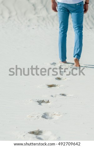 Lonely Man walking on sand  leaving footprint in the sand Desert. Silence, tranquility, freedom.