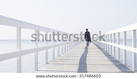 lonely man walking on the pier