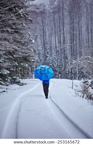 Lonely man with blue umbrella walking trough the forest on the snowy road