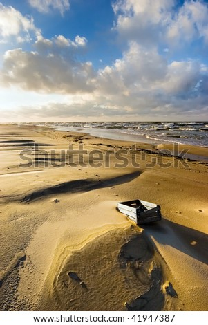 lonely old box on desert beach - stock photo