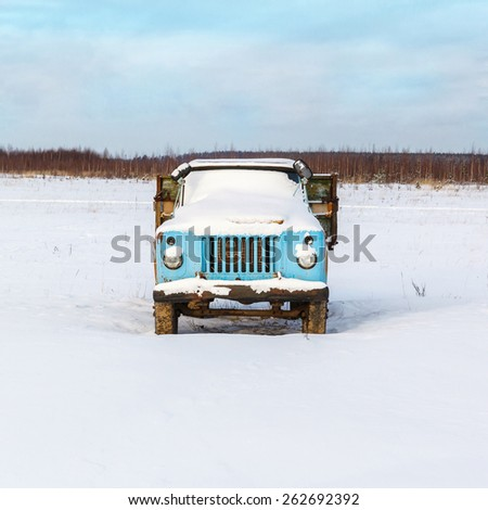 lonely old rusty truck under the snow in an open field - stock photo