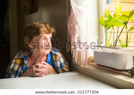 Lonely old woman sitting by the window in his cottage. - stock photo