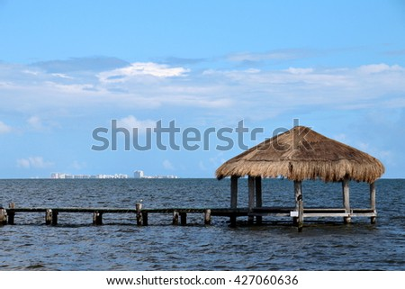 Lonely pavilion at the end of a wooden pier with Cancun, Mexico skyline on the distant horizon. - stock photo