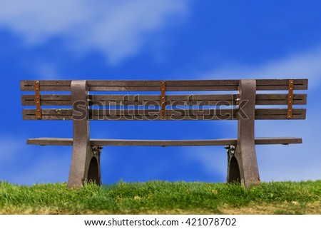 Lonely, peaceful tranquil bench and beautiful summer sky. - stock photo