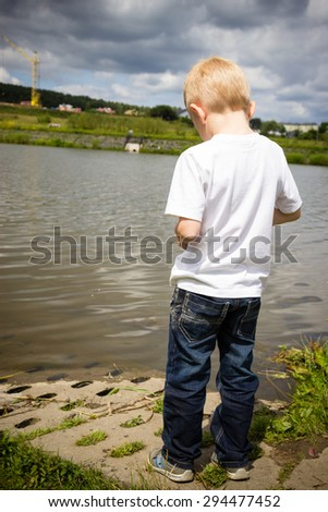 Lonely pensive boy child thinking and daydreaming. Thoughtful kid with head down by river. Solitude, loneliness and rejection concept. - stock photo