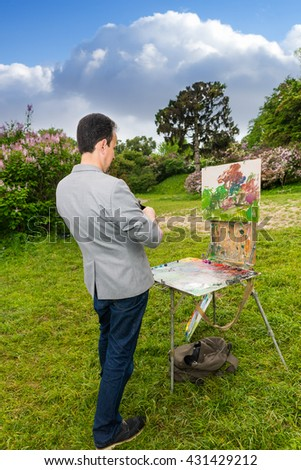 Lonely professional fashionable male painter working outdoors in the garden on a trestle and easel painting with oils and acrylics during an art class - stock photo