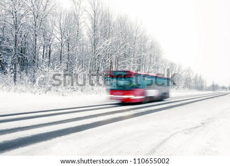 Lonely red bus on small road in winter landscape