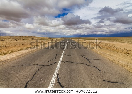Lonely road in the desert under a cloudy sky. - stock photo