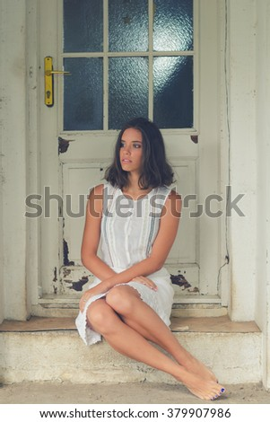 Lonely sad barefoot girl sitting in front of the house in spring. - stock photo
