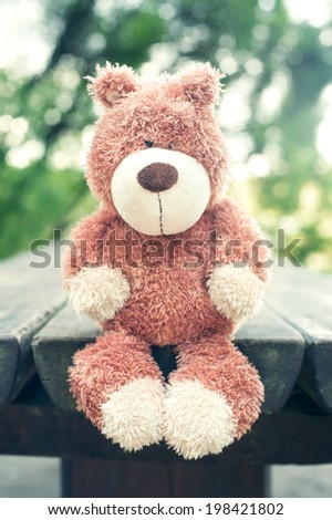 Lonely sad forgotten teddy bear toy on wooden table in the park. Awaiting for owner. Vintage filter. Outdoors. - stock photo