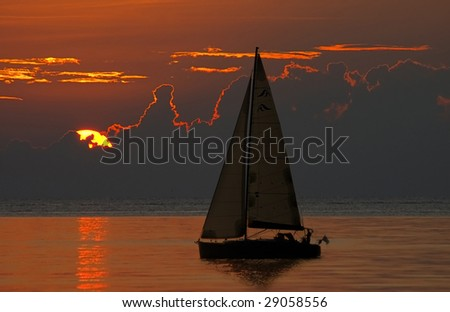 Lonely  sail at infinite ocean beholding of a sunset - stock photo