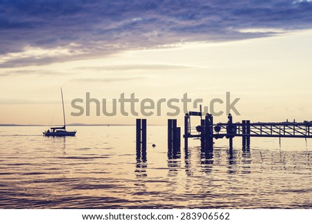 Lonely sailboat, sails to marina on the Constance Lake (Bodensee). Vintage effect. - stock photo