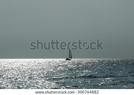Lonely sailing boat. Seascape with the silhouette of sailing ship in dramatic light. - stock photo