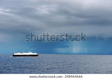 Lonely ship in front of stomy ocean clouds