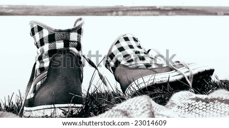Lonely shoes on lake beach in village - stock photo