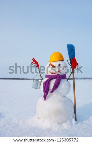 Lonely snowman at a snowy field at winter time