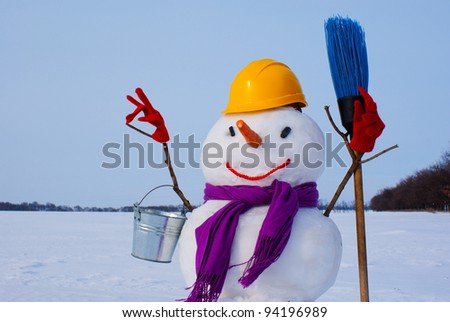 Lonely snowman at a snowy field at winter time - stock photo