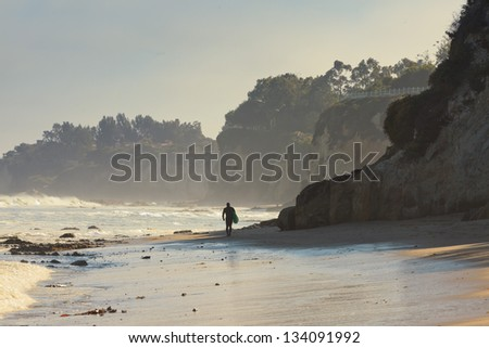 Lonely surfer walking on the beach. Malibu. USA. California. - stock photo
