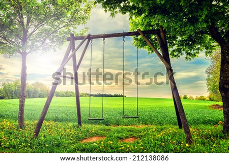Lonely swing at summer sunset   - stock photo