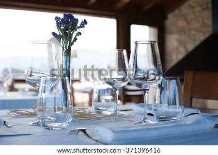 lonely table in elegant luxury restaurant interior with white tablecloth and napkins, silver cutlery, shiny transparent glass and wine cups, crystal vase with green and purple flowers and wooden chair - stock photo