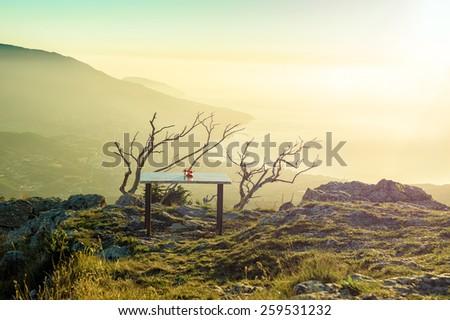 Lonely table in mountains at sunrise. Photo taken on Ay Petri peak, Ukraine. - stock photo