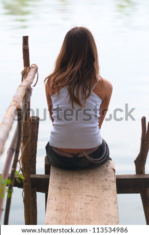 Lonely teenage girl sitting on small dock and looking at the river. - stock photo