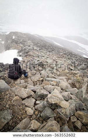 Lonely traveler having a break on the top of the mountain. - stock photo