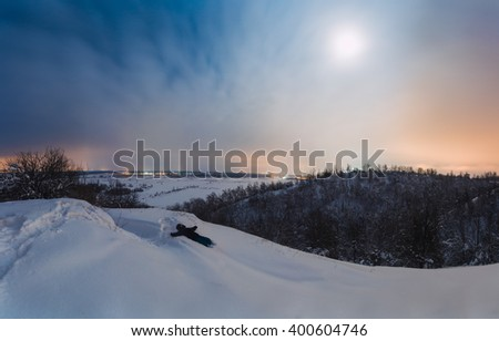 Lonely traveler is relaxing in snow and looking at the moon at night. The man went out of the city for the rest. The man was lost in contemplation. He is enjoying the beautiful night view. - stock photo