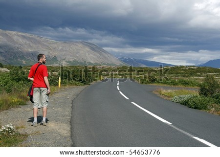 Lonely traveller hitchhiking along the road in beautiful mountainous region of Iceland - stock photo