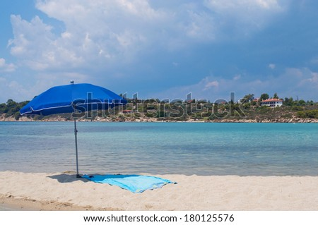 Lonely umbrella and towel on the beach - stock photo
