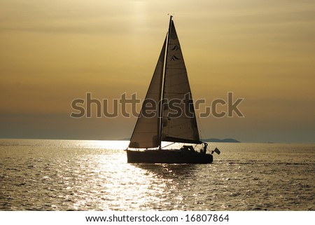 Lonely white sail at infinite ocean on a sunset - stock photo