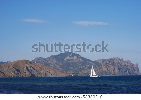 Lonely white yacht in an open sea sailing along the Kara-dag mountain under blue sky - stock photo