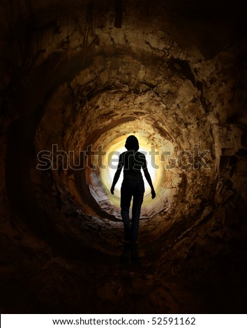 Lonely woman is walking through dark tunnel to the light - stock photo