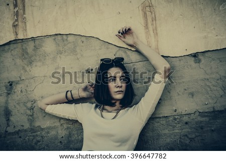 Lonely woman  leaning against concrete wall in urban environment.
