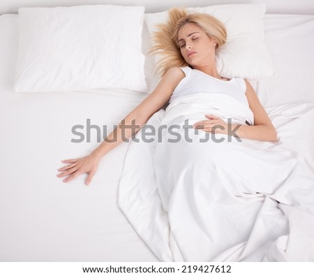 Lonely woman reaching for her husband in empty bedside. - stock photo