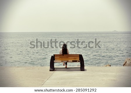 Lonely woman sitting at the sea coast - stock photo