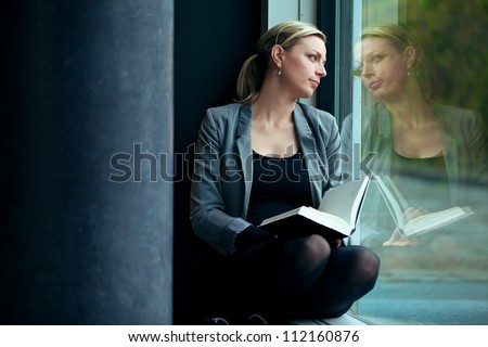 Lonely woman sitting in a windowsill with a book reading and dreaming as she gazes out through the window with a serious expression with copysapce - stock photo