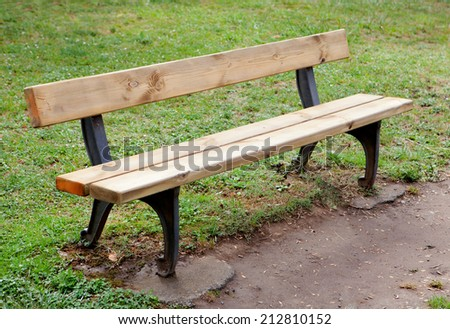 Lonely wooden bench in the park on grass - stock photo