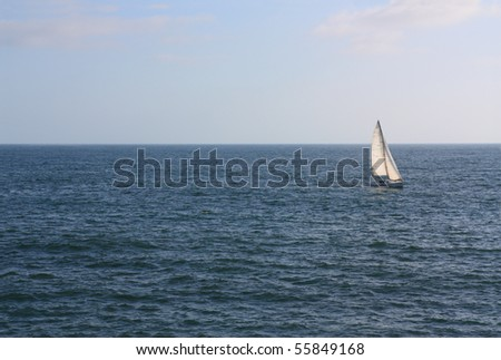 Lonely yacht with white sales in wide open blue ocean waters