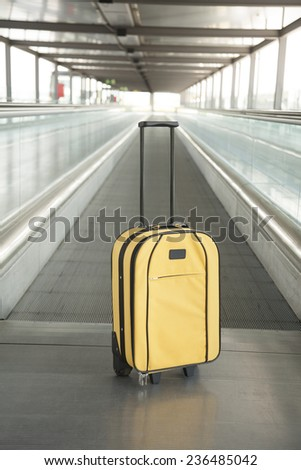 lonely yellow suitcase with black handle at walkway inside airport hall